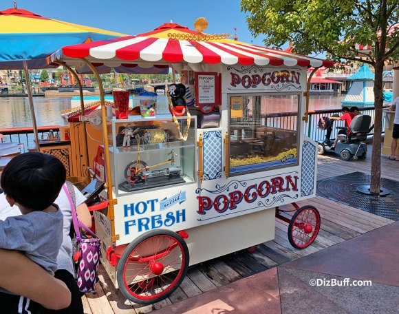 Popcorn vending cart on Pixar Pier in Disney California Adventure featuring Duke Caboom, Canada's most famous stuntman, turning the popcorn canister.