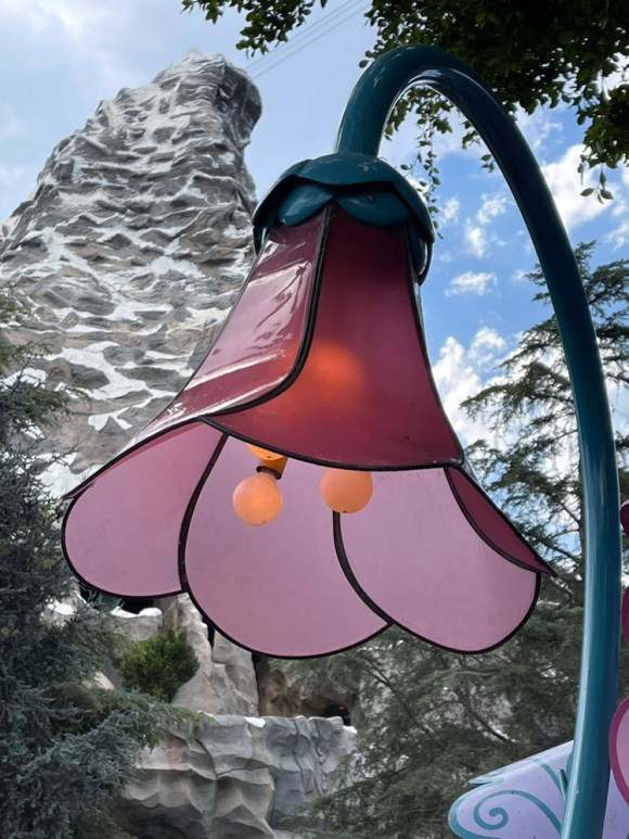 Pink flower light fixture with Matterhorn in background at Alice in Wonderland in Disneyland CA