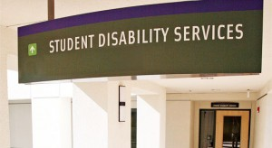 green sign up above head level - student disability services white letters - white stucco corridor leading to brown doors with glass in center