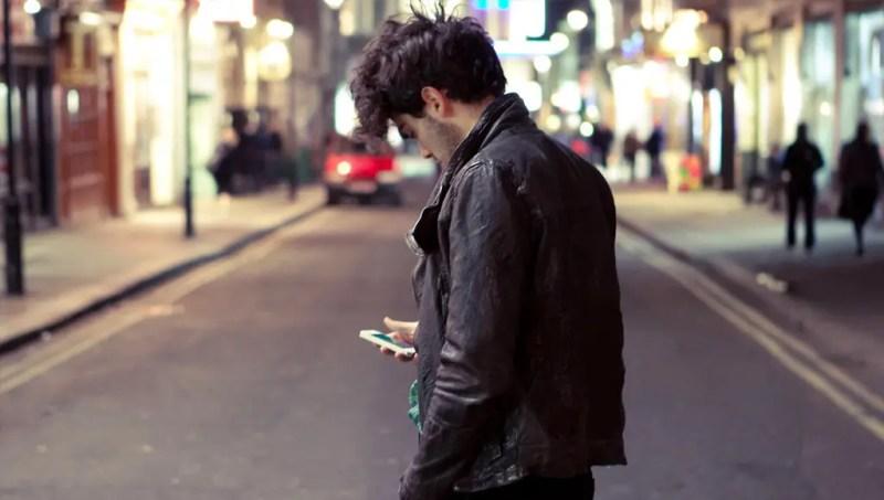 شخص يحمل هاتفا نقالا ويقف في الطريق