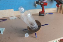 Cut and shape the bottom of the bottle, drill some holes, stick the hanger-sticks through.