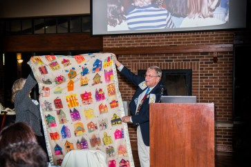 Peggy Dahlquist and Bruce Dahlquist with quilt of children's drawings from students he mentored in School District U-46