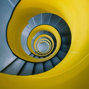 photo looking down into a bright yellow spiral staircase