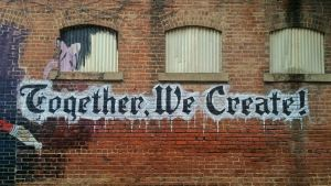 brick wall with graffiti that says Together We Create