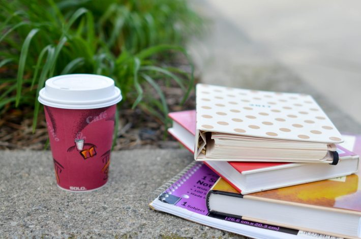 coffee in red paper cup sitting next to pile of books and notebooks