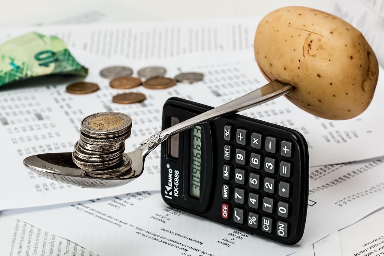 ziemniak i monety na łyżeczce podpartej kalkulatorem