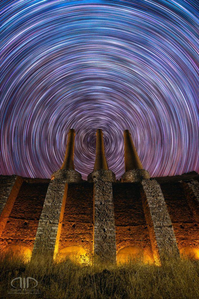 Fotografía nocturna de larga exposición. Traza de estrellas startrail circular con 3 chimeneas de una antigua fábrica abandonada