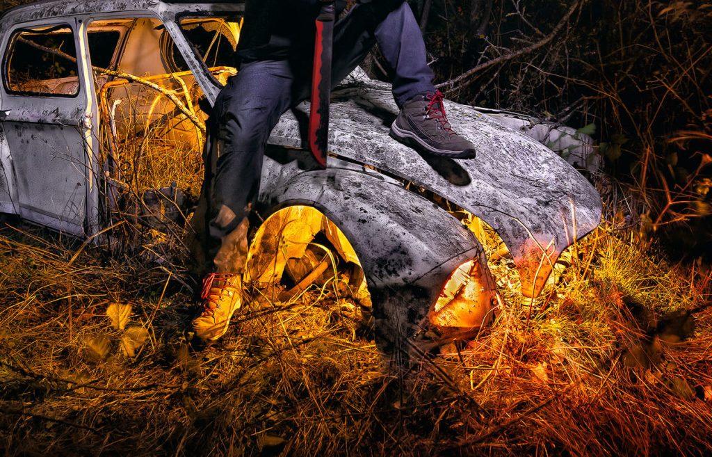 Personaje apocalíptico con máscara de gas y capucha ostiene un machete sobre un coche abandonado