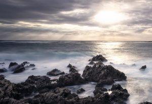 Amanecer en la costa de Menorca. Olas rompiendo contra las piedras mientras sale el sol entre las nubes