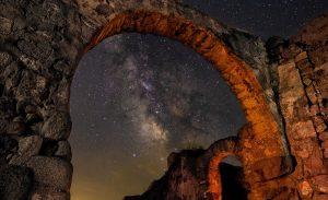 Fotografía nocturna de larga exposición de un arco de una iglesia en ruinas visigoda con la vía láctea cruzando por detrás