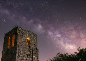 Fotografía nocturna de larga exposición de Vía láctea con una iglesia castillo en ruinas con iluminación nocturna