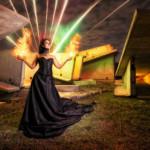 Fotografía de larga exposición nocturna y lightpainting. Modelo con efecto de fuego y fuegos artificiales