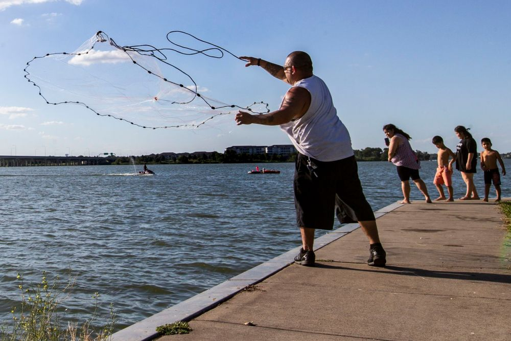 A fisherman, who wished to remain unidentified, casts a net at the John Paul Jones Park along Lake Ray Hubbard in Garland, Texas, on Saturday, July 18, 2020.