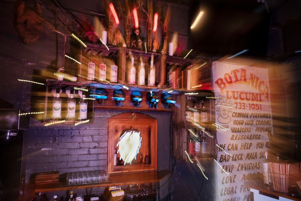 A photograph made with a slow camera shutter behind the bar at the Spirits Room inside Las Almas Rotas in Dallas