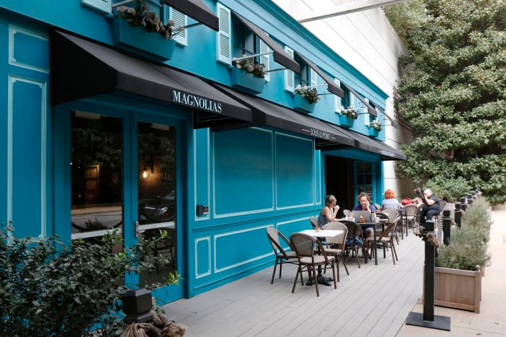 If you've driven through the Harwood District in Dallas, an area near the American Airlines Center, you may have spotted the bright blue exterior of a cafe called Magnolias Sous Le Pont. It has a pretty patio out front, or you can go upstairs to a sizeable green space.