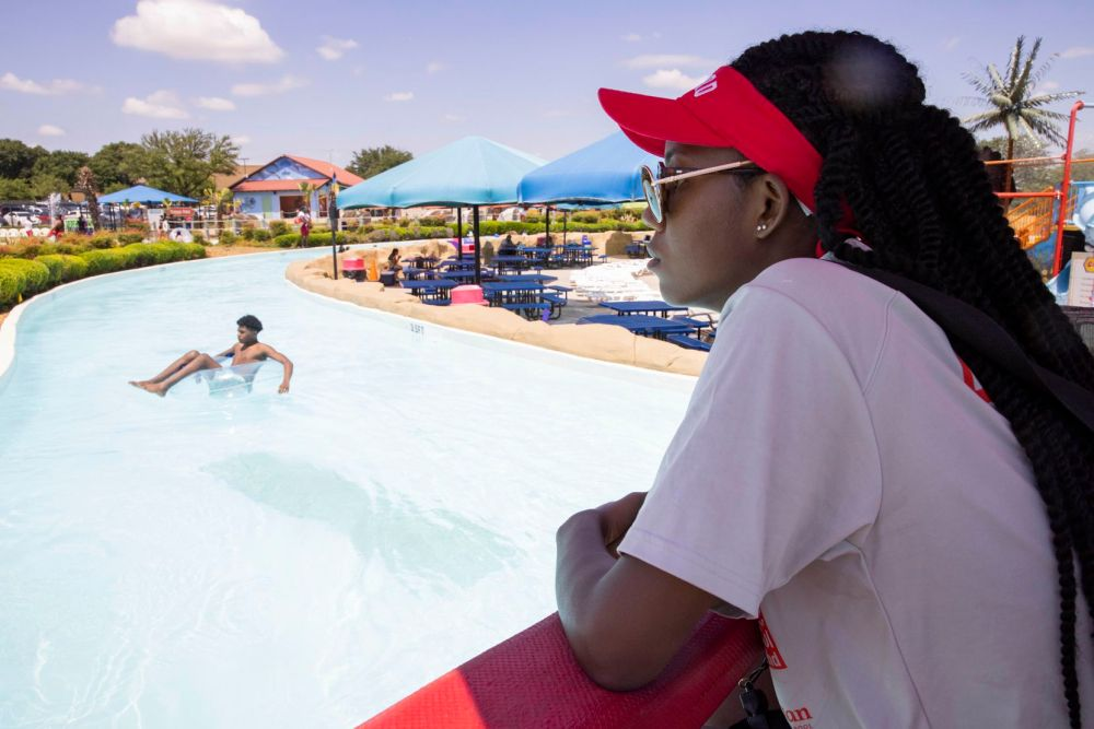 Lifeguard Hope Hart keeps an eye on swimmers at Bahama Beach in Dallas. The water park has three new attractions this year.