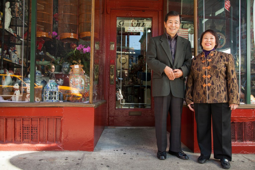 Asian couple in front of their store