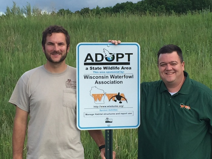 Sam Jonas, DNR wildlife biologist, and Mike Alaimo, WWA Chair for Waukesha County pose next to a sign identifying Rome Pond as a co-managed wildlife area.