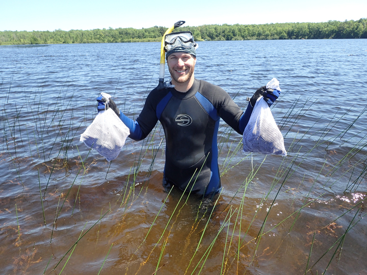 DNR conservation biologist Jesse Weinzinger carries two bags of mussels to identify as part of a statewide survey to better understand the distribution and population of Wisconsin mussel species.