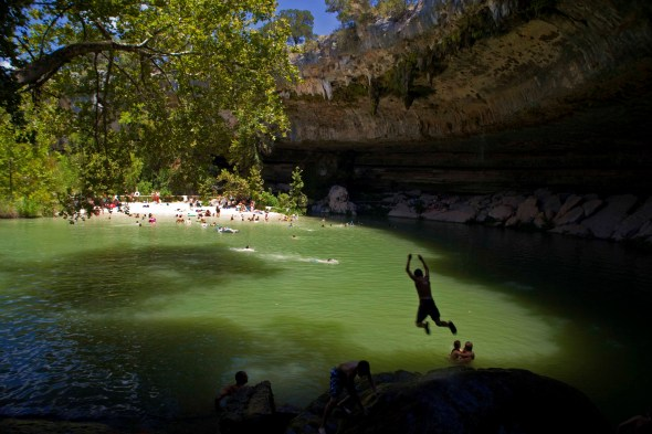 A Swimmer leaps off a cliff at Hamilton Pool Reserve