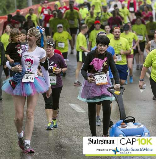 April 12, 2015 - Coral Terry, carries her son, Texas, 2, as her mother, Lindsey Noonan, right, pushes a car stroller down Cesar Chavez on the last mile of the Statesman Cap10k held in Austin, Texas, on Sunday, April 12, 2015. (Rodolfo Gonzalez / AUSTIN AMERICAN-STATESMAN)