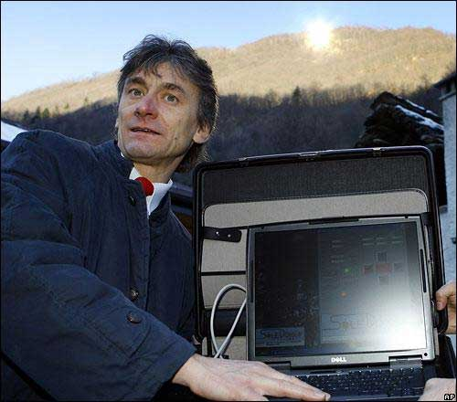 the-mayor-of-viganella-italy-holds-a-computer-that-controls-a-giant-mirror-on-the-hillside-behind