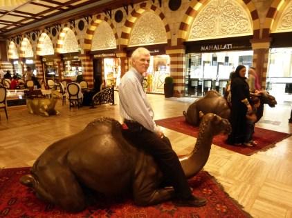 John riding camel in mall