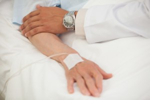 Doctor touching arm of elderly lady in hospital bed