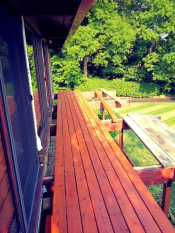 Photo shows newly installed cedar decking with flashing and nailing strip assembly. The first courses have been left off to allow detailing at the edge of the house. Unlike the original installation we will not nail the first course in to the house sill. In keeping with contemporary practice we will allow ample space for air flow between the house and the start of the decking.