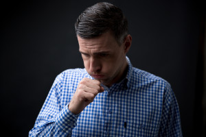 Portrait of a man coughing over black background