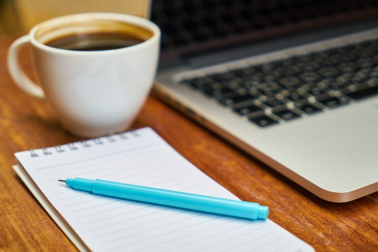 pad of paper, pen, coffee cup and corner of a laptop on a desk