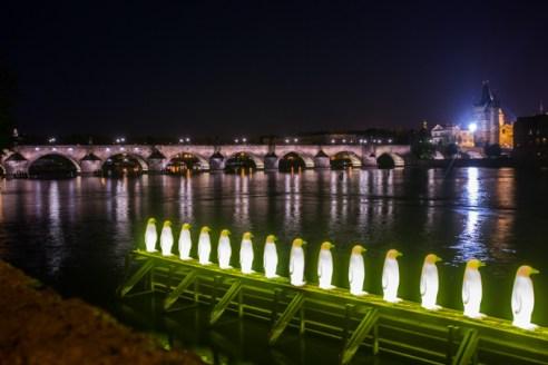 Instalación sobre el río y, al fondo, el puente de Carlos.