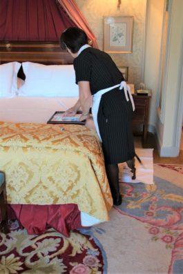 """Intentando ayudar a la señora a hacer la cobertura o """"turn down"""" de la cama."""