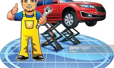Car Mechanic With Wrench Standing On Background Of Car On A Lift.
