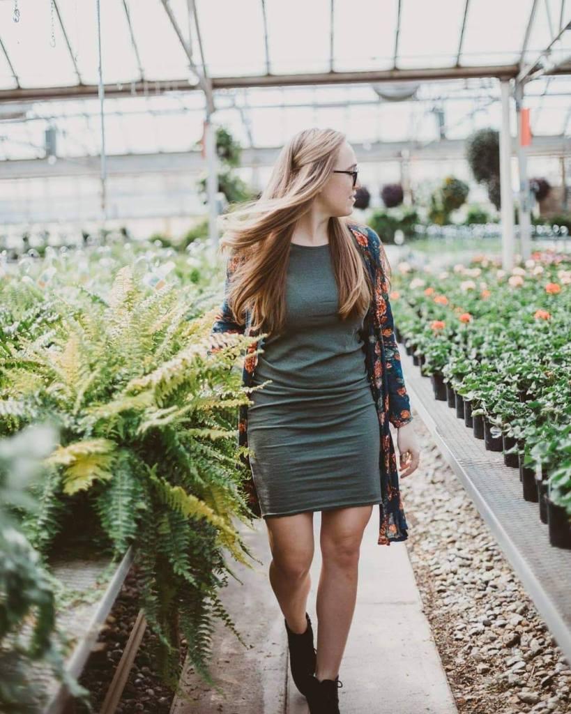 attractive long hair blonde girl in green dress at a greenhouse indoor gardener
