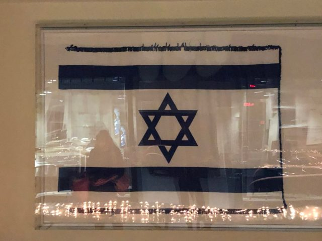 Israeli flag with reflection of candles