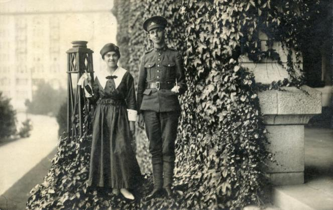 A couple pose on the ivy-covered verandah of the Empress Hotel