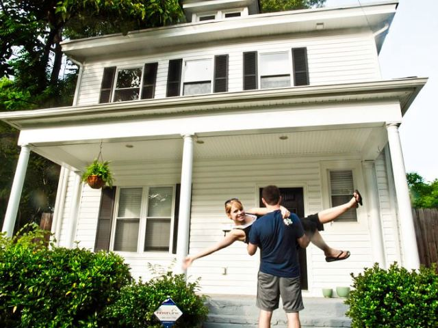 young couple celebrating being new home owners in front of their new, white house