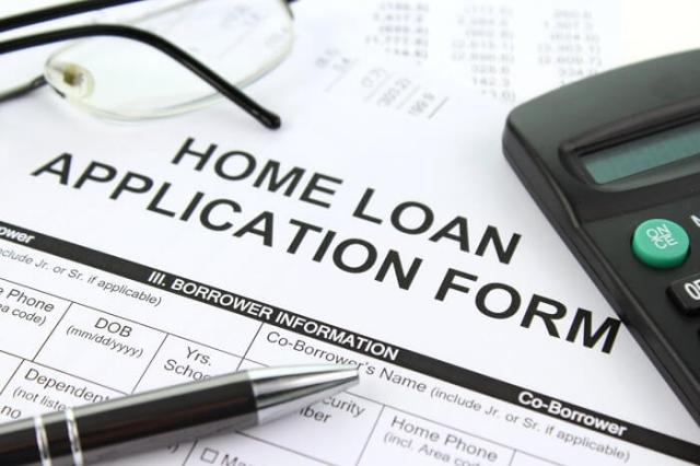 home loan application form on table with pen, calculator