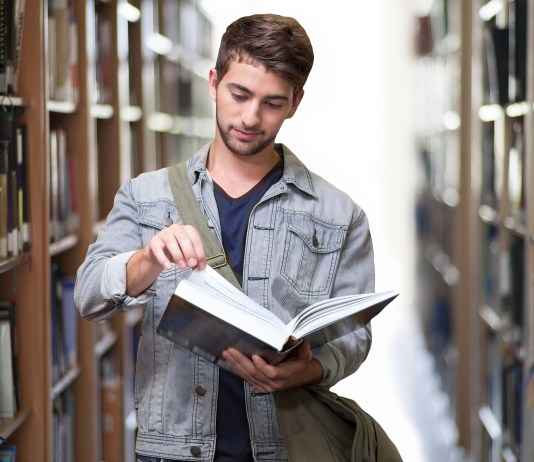 A male college student standing in a library, reading a book. With the Discover Student Card he could by that book