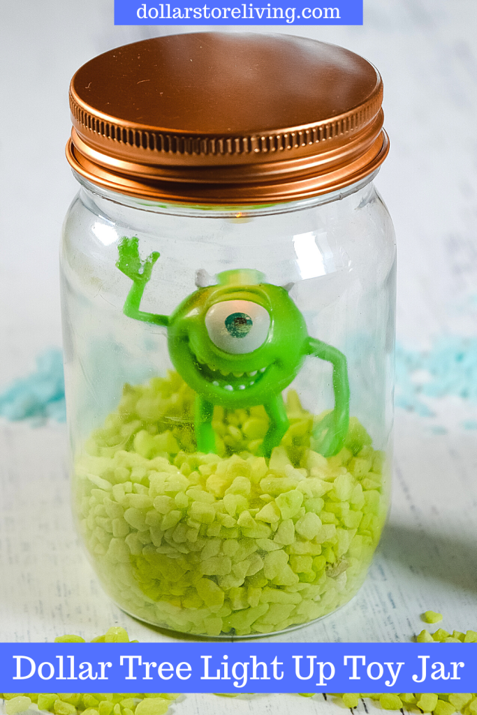The finished version of the toy jar with Mike from Monsters Inc. on top of green pebbles sealed up in a plastic mason jar.