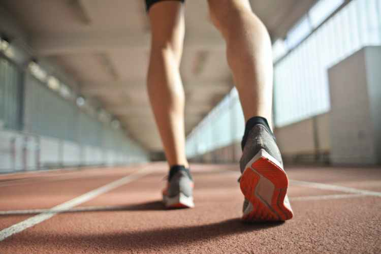 fit runner standing on racetrack in athletics arena