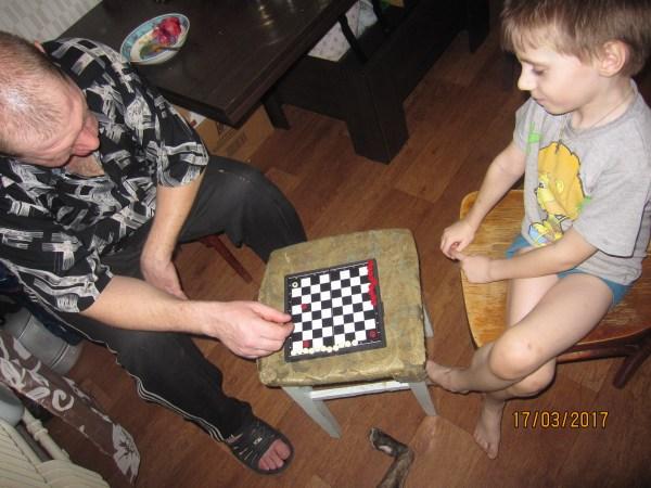 Папа играет с Егором в шашки