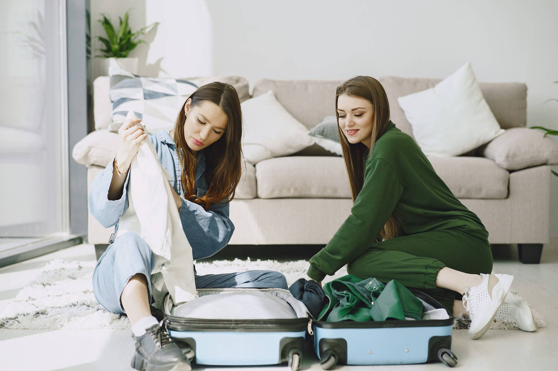 positive women unpacking luggage in hotel