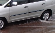 Water pours out of car doors as it arrives out of the street to Paladian Park