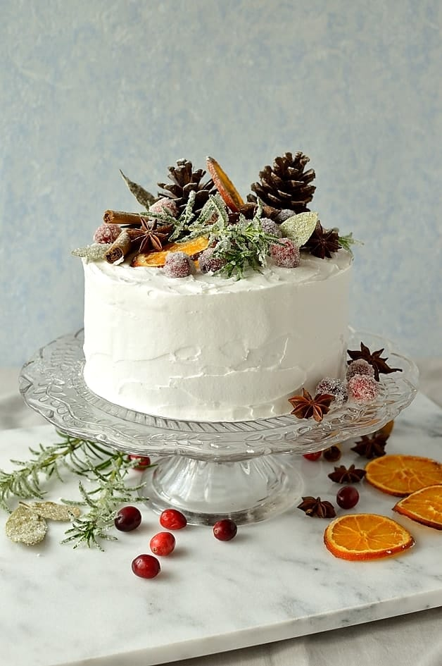 Moist, gingery Christmas fruitcake topped with marzipan, royal icing and rustic decorations of sugared cranberries, rosemary and bay leaves, dried orange slices, pine cones and whole spices.