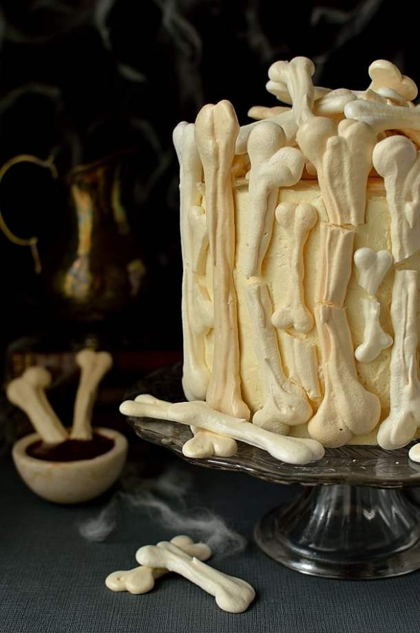 Meringue bone garden Halloween cake - moist chocolate cake filled with vanilla swiss meringue buttercream and raspberry jam covered in meringue bones with berry coulis 'blood' on the side (graveyard cake)