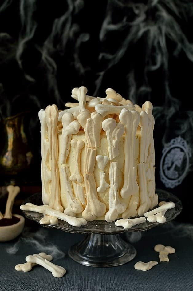 meringue bone palace halloween cake - moist chocolate cake filled with vanilla swiss meringue buttercream and raspberry jam covered in meringue bones with berry coulis blood on the side