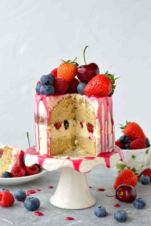 Mini white chocolate berry drip cake - delicious, moist vanilla cake with whipped white chocolate gananche, pink white chocolate drip and fresh berries; serves just 2-4 people!