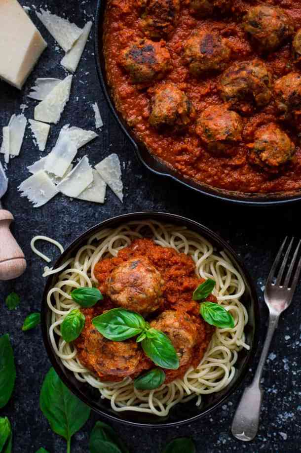 Vegetarian mushroom meatballs with tomato sauce, spaghetti, basil and cheese in a black bowl next to a skillet